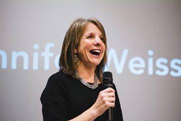Speaker holding microphone wearing a black dress.